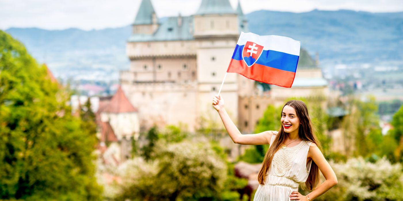 turystka z flagą słowacką na tle zamku Bojnice.
